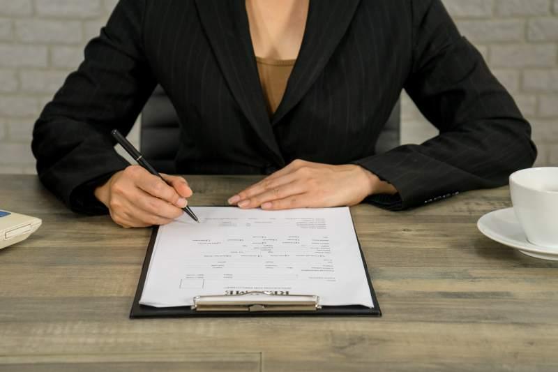 business woman write resume for applying the job